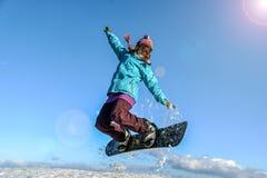 Mujer joven en el salto de la snowboard Fotografía de archivo