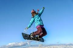 Mujer joven en el salto de la snowboard Imagen de archivo libre de regalías