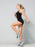 Mujer joven en el salto negro de la ropa de deportes Foto de archivo