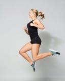 Mujer joven en el salto negro de la ropa de deportes Imágenes de archivo libres de regalías