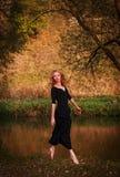 Mujer joven en el salto negro del vestido Imagen de archivo