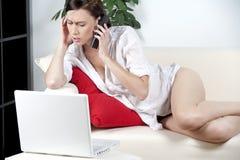 Mujer joven en el sofá usando la computadora portátil Imagenes de archivo