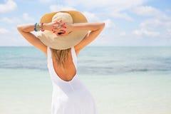 Mujer joven en el sombrero blanco del vestido y de paja en la playa Foto de archivo libre de regalías