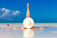 Mujer joven en el sombrero de paja que pone en la playa y el enjoyi tropicales