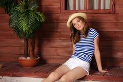 Mujer joven en el sombrero de paja que se sienta cerca de casa de planta baja de madera imagen de archivo