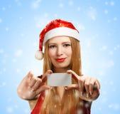 Mujer joven en el sombrero de Papá Noel con la tarjeta de felicitación de la Navidad Fotos de archivo libres de regalías