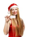 Mujer joven en el sombrero de Papá Noel con la tarjeta de la invitación de la Navidad Foto de archivo