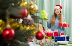 Mujer joven en el sombrero de Papá Noel con los regalos de Navidad dentro Imagen de archivo libre de regalías