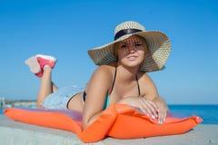 Mujer joven en el sombrero del sol que miente en balsa de la piscina Fotografía de archivo libre de regalías