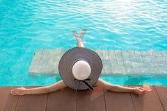 Mujer joven en el sombrero grande que se relaja en la piscina, Imagen de archivo libre de regalías
