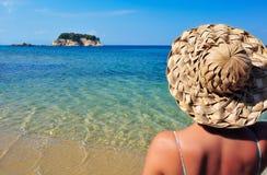 Mujer joven en el sombrero que mira la pequeña isla Foto de archivo