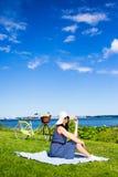 Mujer joven en el sombrero que se sienta en la costa de mar con la bicicleta del vintage Imagen de archivo