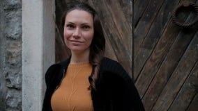 Mujer joven en el suéter anaranjado que se coloca en la puerta y las sonrisas de madera almacen de metraje de vídeo