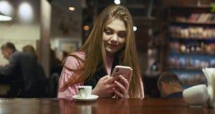 Mujer joven en el suéter color de rosa que sostiene un smartphone en manos y que mecanografía en su pantalla mientras que charla  metrajes