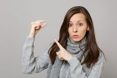 Mujer joven en el suéter gris, bufanda señalando el dedo índice en la píldora de aspirin de la tableta de la medicación aislada e imagen de archivo libre de regalías