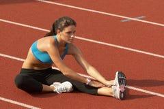 Mujer joven en el sujetador de los deportes que estira la pierna en pista Fotos de archivo libres de regalías