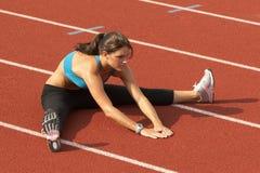 Mujer joven en el sujetador de los deportes que estira las piernas en pista Imagenes de archivo