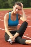 Mujer joven en el sujetador de los deportes que se reclina sobre pista Imágenes de archivo libres de regalías