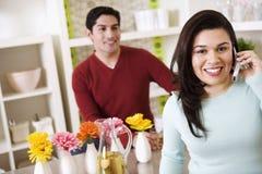 Mujer joven en el teléfono celular con el marido que mira encendido Imagenes de archivo