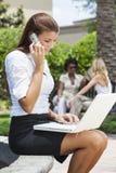 Mujer joven en el teléfono celular usando el ordenador portátil Foto de archivo