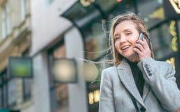 Mujer joven en el teléfono Ciérrese para arriba del smartphone usado por la muchacha rubia fotografía de archivo