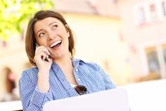 Mujer joven en el teléfono con el ordenador portátil imagen de archivo