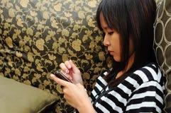 Mujer joven en el teléfono en su sofá Foto de archivo
