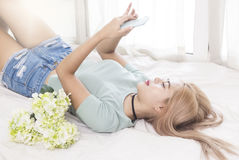 Mujer joven en el teléfono móvil del uso de la cama imagenes de archivo