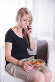 Mujer joven en el teléfono que come los dulces Imagenes de archivo