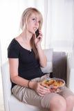Mujer joven en el teléfono que come los dulces Fotos de archivo
