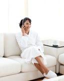 Mujer joven en el teléfono que se sienta en el sofá Imagen de archivo libre de regalías
