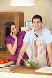 Mujer joven en el teléfono y el hombre joven en cocina Fotografía de archivo libre de regalías