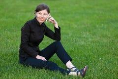 Mujer joven en el teléfono que se sienta en hierba Fotografía de archivo libre de regalías