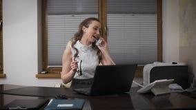 Mujer joven en el trabajo, hablando en el teléfono con su novia y risas La muchacha lleva a cabo una posición de la administració almacen de video
