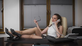 Mujer joven en el trabajo, hablando en el teléfono con su novia y risas La muchacha lleva a cabo una posición de la administració metrajes