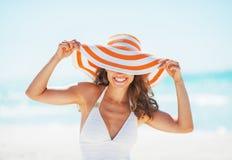 Mujer joven en el traje de baño que oculta detrás del sombrero de la playa Imagenes de archivo