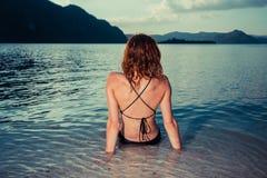 Mujer joven en el traje de baño que se sienta en la playa tropical Foto de archivo libre de regalías