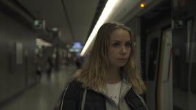 Mujer joven en el tren que espera de la estación de metro en la plataforma Mujer joven del viajero en metro Muchacha en metro del almacen de metraje de vídeo