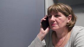 Mujer joven en el tren que habla en el teléfono almacen de video