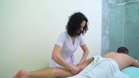 Mujer joven en el uniforme que hace masaje de relajación en muslo del hombre en salón del balneario almacen de metraje de vídeo
