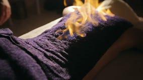 Mujer joven en el vector del masaje El hombre la cubre con una toalla y fija el fuego a él metrajes
