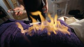 Mujer joven en el vector del masaje El hombre la cubre con una toalla y fija el fuego a él almacen de video