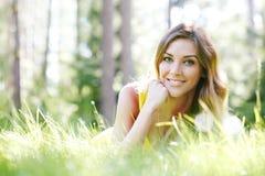 Mujer joven en el vestido amarillo que miente en hierba Fotos de archivo