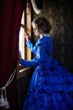 Mujer joven en el vestido azul del vintage que coloca la ventana cercana en cupé Imagenes de archivo