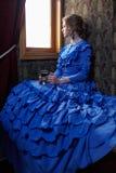 Mujer joven en el vestido azul del vintage que se sienta en cupé del rai retro fotografía de archivo