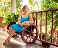 Mujer joven en el vestido azul que se relaja en terraza de la casa Imagen de archivo libre de regalías