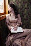 Mujer joven en el vestido beige del vintage de la lectura del comienzo del siglo XX foto de archivo libre de regalías
