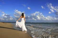 Mujer joven en el vestido blanco en una playa Fotos de archivo