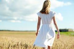 Mujer joven en el vestido blanco que camina adelante en campo Fotos de archivo libres de regalías