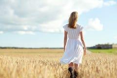Mujer joven en el vestido blanco que camina adelante en campo Imagenes de archivo